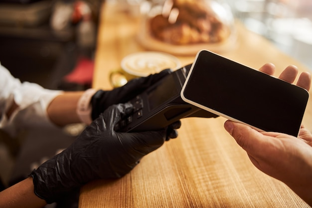 현대적인 도시 카페에서 전자 지불 기계에 가까운 고객