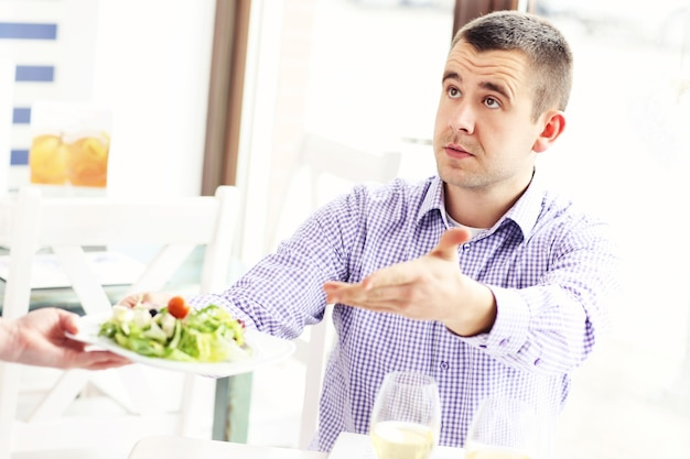 A customer coplaining about the food in a restaurant