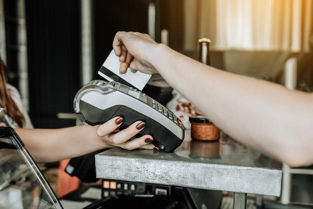 카페에서 신용카드 결제를 하는 고객. 쇼핑, 전자 상거래, 은행, 인터넷 상점, 돈 개념 지출