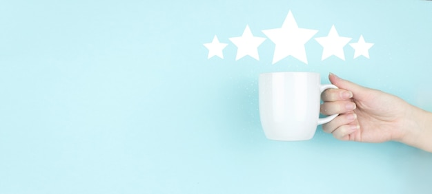 Customer experience concept. girl hand hold morning coffee cup with five stars 5 rating sign icon on blue background. increase rating evaluation and classification concept.