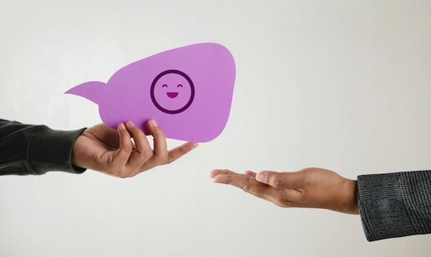 Концепция клиентского опыта. счастливый клиент, дающий бизнесмену улыбающийся смайлик. отзыв о bubble speech card. положительный отзыв. исследование удовлетворенности