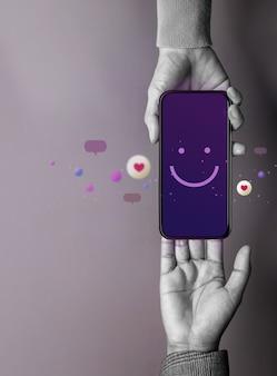 Концепция клиентского опыта. счастливый клиент, дающий бренду улыбающийся смайлик через мобильный телефон. отзыв о смартфоне. положительный отзыв. онлайн-опрос удовлетворенности