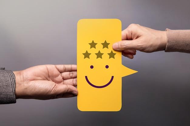 Customer experience concept. happy client giving a five star rating and smiling face feedback on bubble speech card to a businessman. positive review. satisfaction survey. high best excellent score