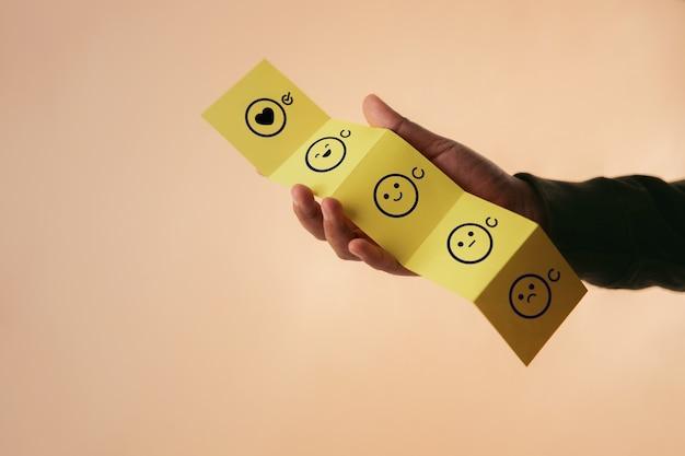 고객 경험 개념. 접힌 종이에 긍정적 인 리뷰를주는 행복한 클라이언트. 나쁨에서 우수로 피드백 아이콘