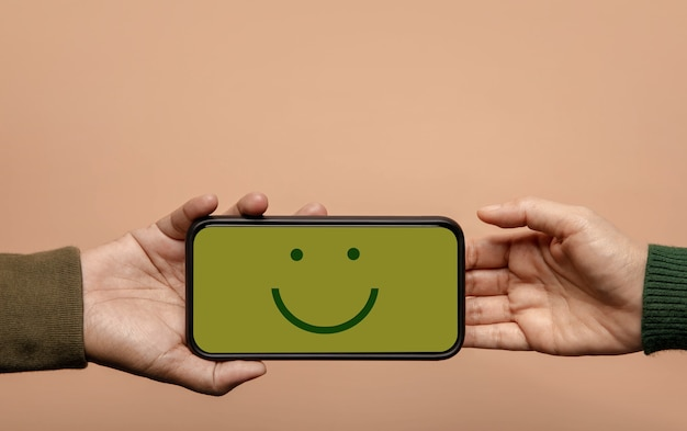 Customer experience concept. happy client giving a smiling emoticon via mobile phone to brand. feedback on smartphone. positive review. satisfaction survey