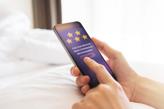 Customer Experience Concept. Happy Client Using Smartphone on Bed