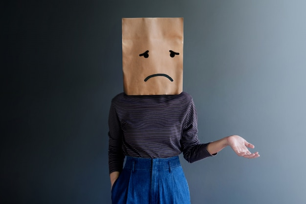 Customer experience or human emotional concept. woman covered her face by paper bag and present sadness feeling and disappointed by drawn line cartoon and body language