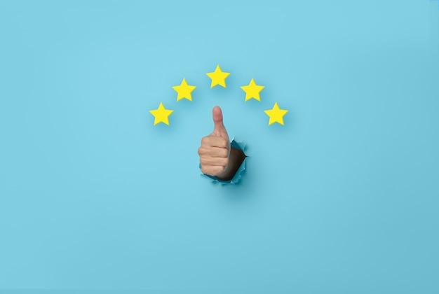 カスタマーエクスペリエンス女性は、青い背景の5つ星の優れた評価に賛成票を投じます。レビューとフィードバックの概念。