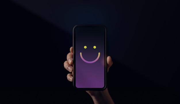 カスタマーエクスペリエンスの概念。笑顔の絵文字で携帯電話を持っている手。肯定的なレビューフィードバックを与える幸せな顧客。クライアント満足度調査