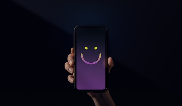 Customer experiences concept. hand holding  a mobile phone with smiling face emoticon. happy customer giving a positive review feedback. client satisfaction surveys