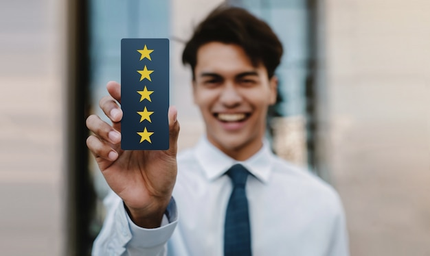 Customer experiences concept. happy young businessman giving five stars rating and positive review on card. client's satisfaction surveys. front view