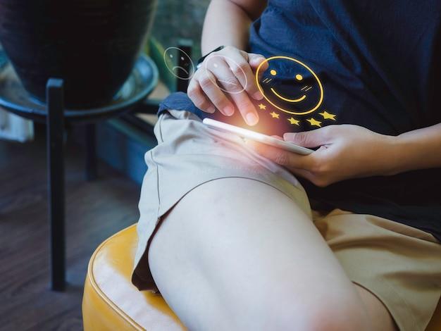 Концепция клиентского опыта. женская рука дает улыбающийся рейтинг смайлика и пятизвездочный символ, положительный отзыв через смартфон для обратной связи, службы удовлетворенности дома.