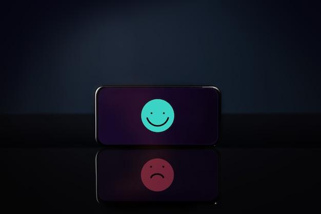 カスタマーエクスペリエンスまたはメンタルヘルスの概念。携帯電話の笑顔の漫画は悲しみの顔を反映しています。スマートフォンに関するフィードバック。ポジティブおよびネガティブレビュー。オンライン満足度調査
