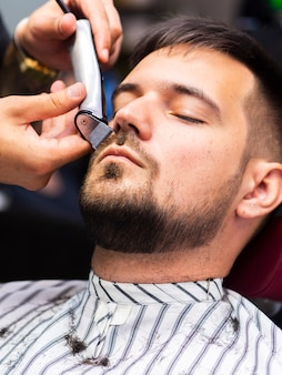 Customer getting his beard trimmed
