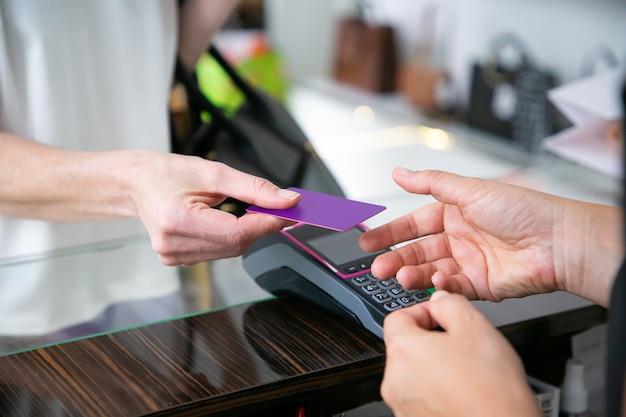 支払いのためにpos端末を備えたデスクでレジ係にクレジットカードを渡す顧客。クロップドショット、手のクローズアップ。ショッピングのコンセプト