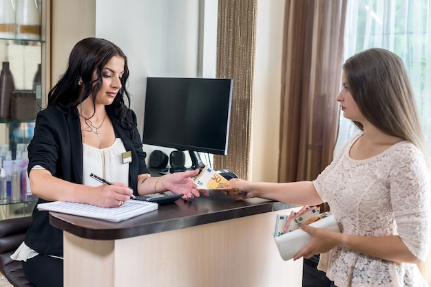Customer giving euro banknotes to administrator in beauty salon