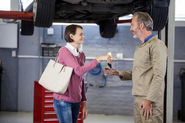 Dando al cliente le chiavi dell'auto al meccanico