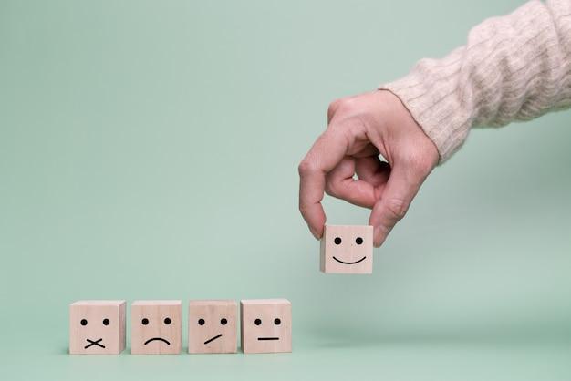 고객의 손이 행복한 얼굴을 선택합니다. 서비스, 설문 조사, 요금 커뮤니케이션 개념