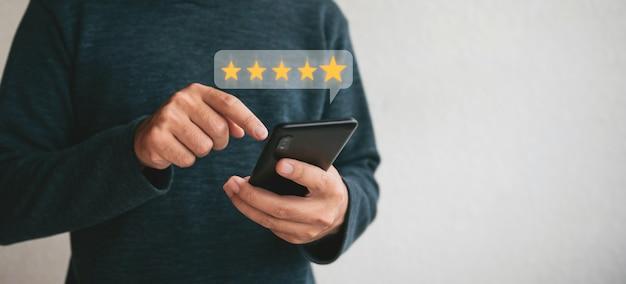 Рука клиента, держащая смартфон и пять звезд с копией пространства. рейтинг лучших отличных услуг по удовлетворенности. концепция удовлетворенности клиентов.