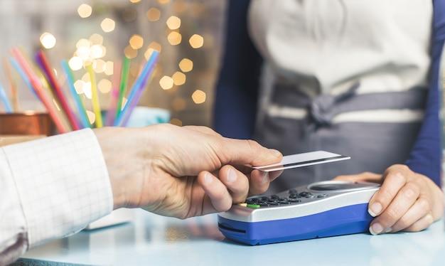 Рука клиента оплачивается кредитной картой в магазине по технологии nfc. оплата счета бесконтактной технологией.