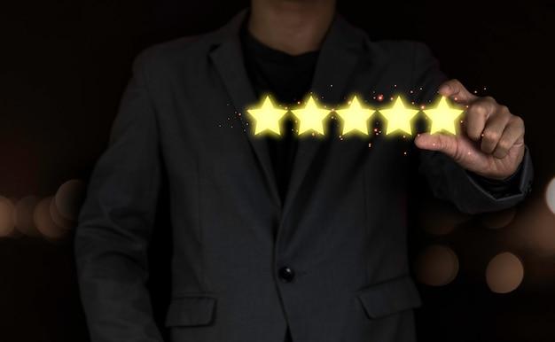 黄色のイラストに5つ星仮想スクリーニングモニターを置く顧客の手