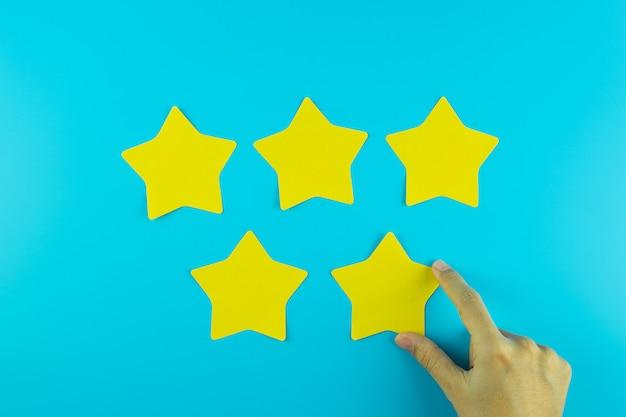 파란색 바탕에 5 개의 별 노란 종이 노트를 들고 고객. 고객 리뷰, 피드백, 평가, 순위 및 서비스 개념.
