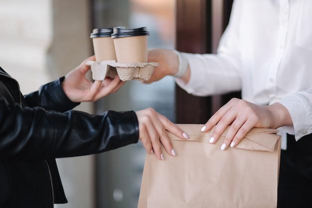 Клиент в маске встает на улице и берет пакет с кофе и едой у кассира в маске на
