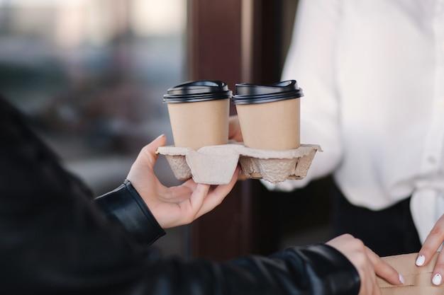 Клиент в маске стоит на улице и берет пакет с кофе у кассира в маске в кафе