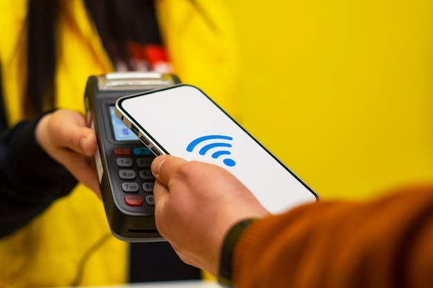 顧客は、nfcテクノロジーを使用して店内でスマートフォンを使用して支払いを行っています。決済端末と売り手の女の子を背景に。
