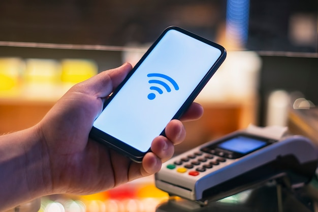 顧客は、nfcテクノロジーを使用して店内でスマートフォンを使用して支払いを行っています。決済端末の背景に対して。