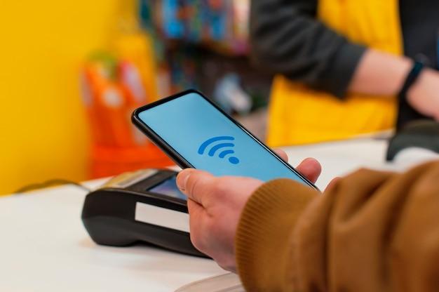顧客は、決済端末のnfcテクノロジーと売り手の女の子を使用して店内でスマートフォンで支払いを行っています
