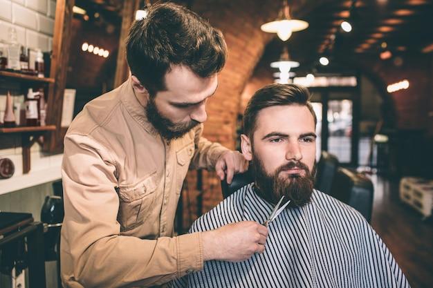 Клиент сидит в кресле и смотрит прямо вперед с серьезным взглядом. его авиастроитель подстригает бороду ножницами.