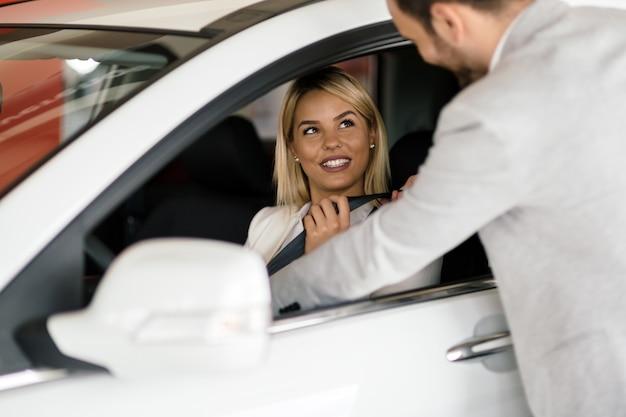 Клиент смотрит на автомобили в автосалоне и разговаривает с продавцом