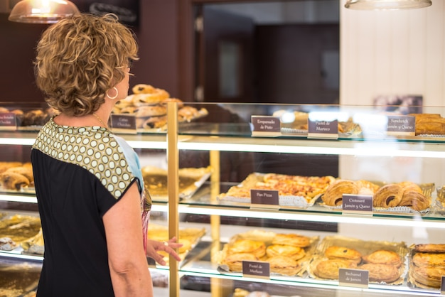 Customer looking at cakes in a bakery to buy