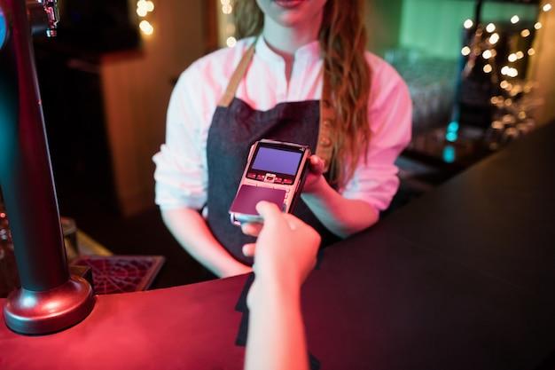Cliente che effettua il pagamento tramite carta di credito allo sportello