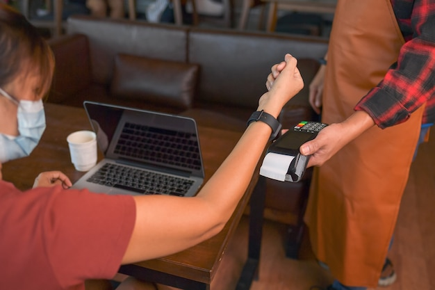 Customer making wireless or contactless payment using smartwatch. store worker accepting payment over nfc technology.shallow depth of field
