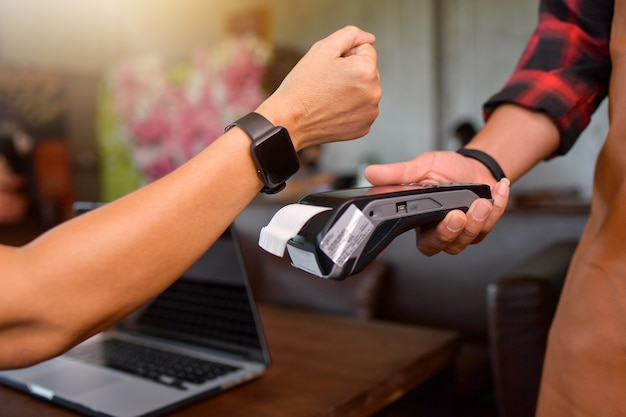 Customer making wireless or contactless payment using smartwatch