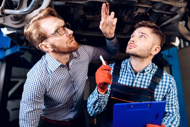 Customer and mechanic are cheking car details.