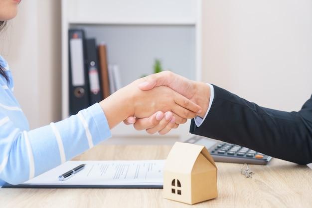 顧客または女性が新しい家のコンセプトを購入するためのローン契約に署名すると言う