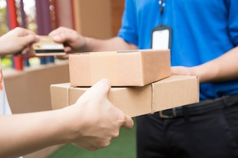 Customer paying by credit card for shipping product and sending to shipping man