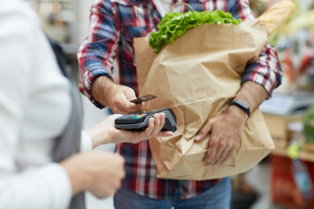 Customer paying by nfc in supermarket