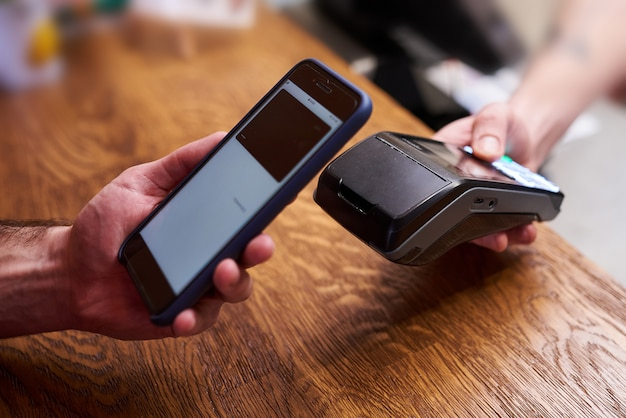 Customer paying by smartphone with nfc technology