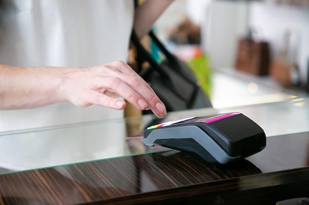 고객이 옷가게에서 신용 카드로 결제하고 비밀번호를 입력합니다. 자른 샷, 손의 근접 촬영입니다. 쇼핑 또는 구매 개념