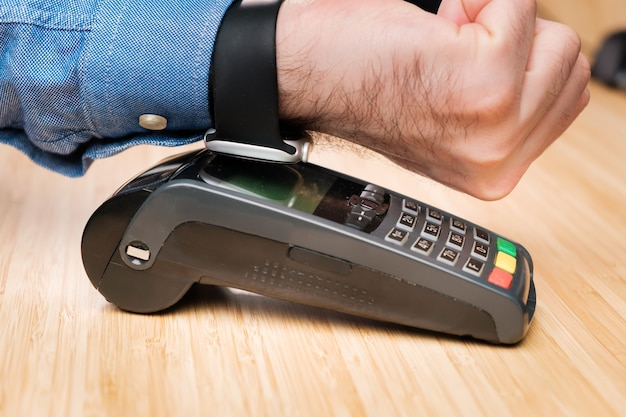 Customer paying through smartwatch using nfc technology contactless payment terminal machine