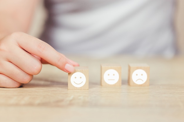 Customer pressing smiley face emoticon on wood cube.