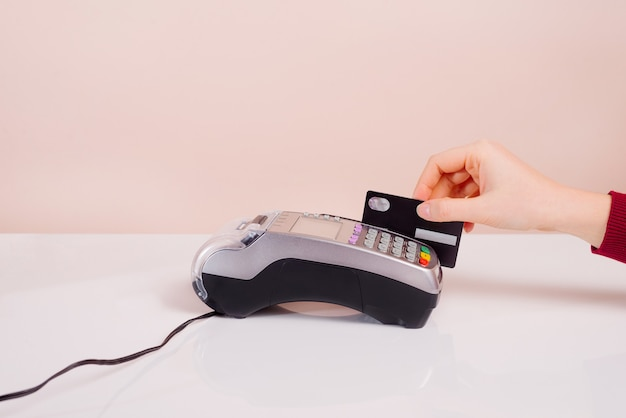 Customer's hand near the bar makes payment by credit card by terminal, view of hand device