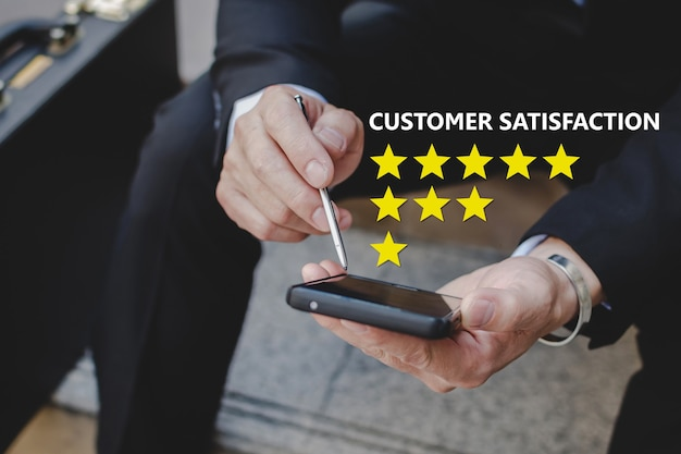 顧客満足。良い評価、顧客レビュー、デジタルマーケティング、チェックリストの計画、良い経験、顧客フィードバックの概念をレビューするために携帯電話でスタイラスペンを使用しているビジネスマンの投資家