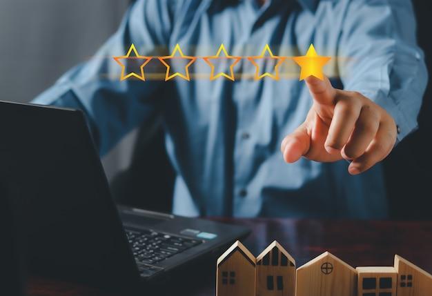 顧客満足の概念。手で星を置いて5つ星を完成させます。 5つ星の評価を与えます。サービス評価、満足度の概念。