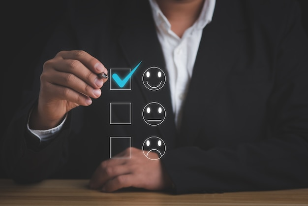 顧客満足度調査の概念。幸せなアイコンで評価を与えるビジネスマン。