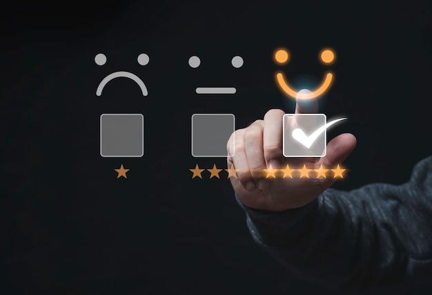 Концепция опроса удовлетворенности клиентов, бизнесмен трогательный значок смайлика с желтыми пятью звездами и правильная отметка для оценки продукта и услуги.
